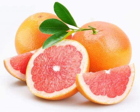 toronja: Grupo de pomelos con hojas sobre un fondo blanco.
