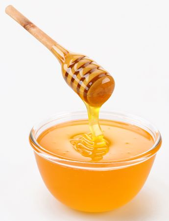 glass of bowl: Honey pouring from stick to the bowl