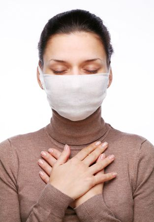 Young woman in medical mask keeping hands on chest Stock Photo - 5853591