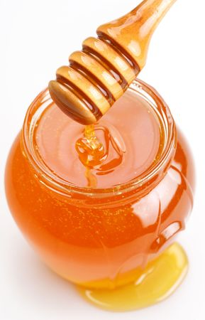Full honey pot and spilled honey on a white background. photo