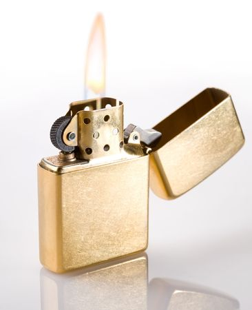 Flaming golden lighter on a white background photo