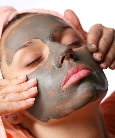 Beauty-spa. Applying of cosmetic mud mask. Close face of young woman photo