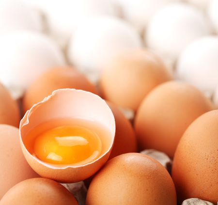 broken brown egg is among the whites of eggs. photo