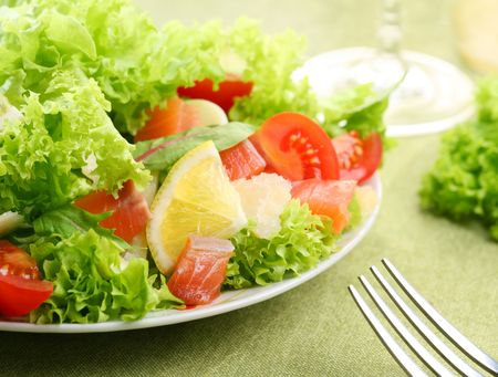 Fresh salad with tomatoes and salmon in a white bowl on a green tablecloth Stock Photo - 6305929
