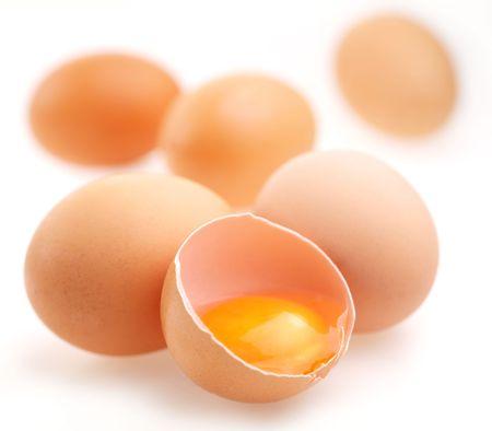 Mit braunen Eier auf einem weißen Hintergrund. Ein Ei ist unterbrochen.