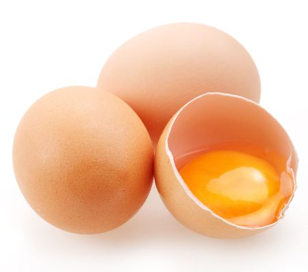 yolks: With brown eggs on a white background. One egg is broken.