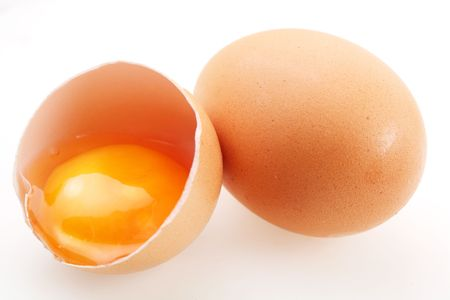 With brown eggs on a white background. One egg is broken. photo