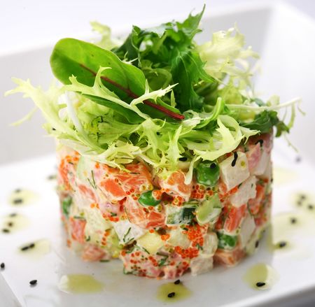 Salad with salmon, caviar and arugula on a white background photo