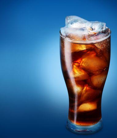 carbonation: Vidrio de cola con hielo sobre un fondo azul