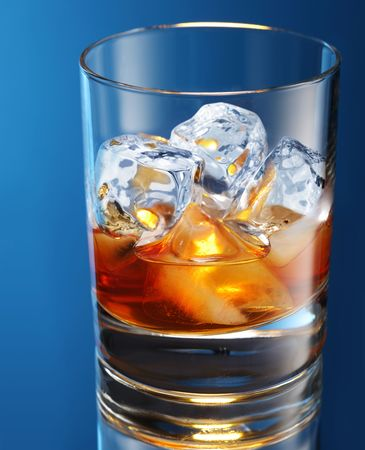carbonation: Glass of brandy with ice cubes isolated on a blue