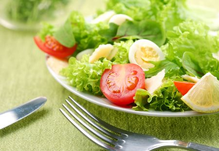 salad fork: Fresh salad with tomato and quail eggs in a white bowl on a green tablecloth