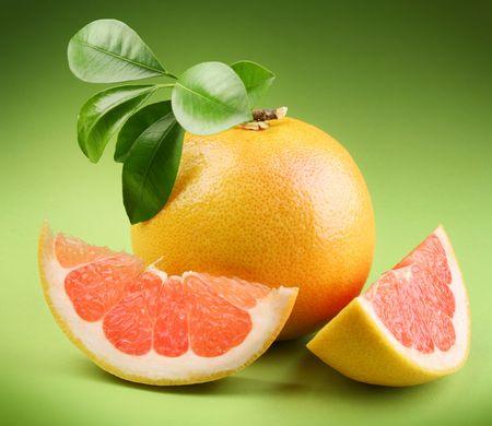segment: Ripe grapefruit with segment on a green background