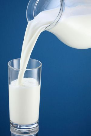 Pouring of milk from jug into a glass Stock Photo - 6608204