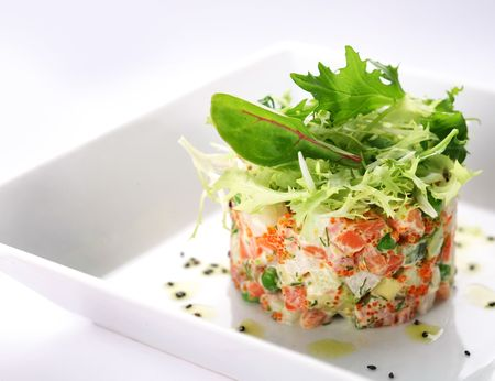 atún: Ensalada de salmón, caviar y rúcula sobre un fondo blanco