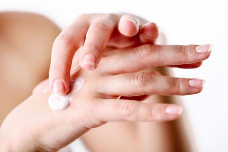 Young woman cares about her hands, applying cream on them. photo