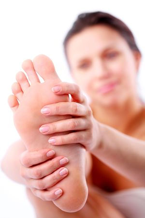 indulgere: Giovane donna massaggia il suo piede. Su uno sfondo bianco.