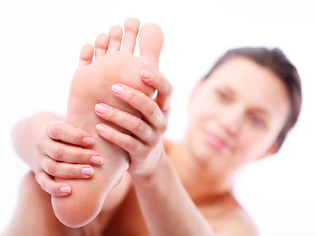 Young woman massages her foot. On a white background. Stock Photo - 7512147