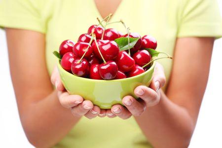 Crockery with cherries in woman hands. photo