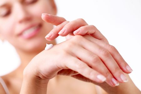 Smiling young woman applies cream on her hands. On a white background. photo