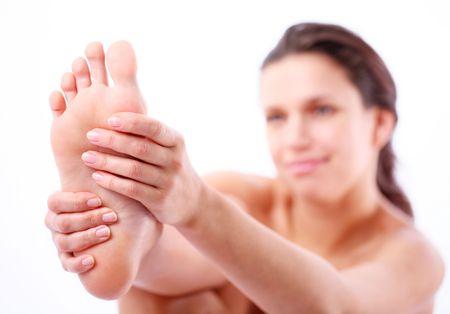flujo: Mujer joven masajes su pie. Sobre un fondo blanco.  Foto de archivo
