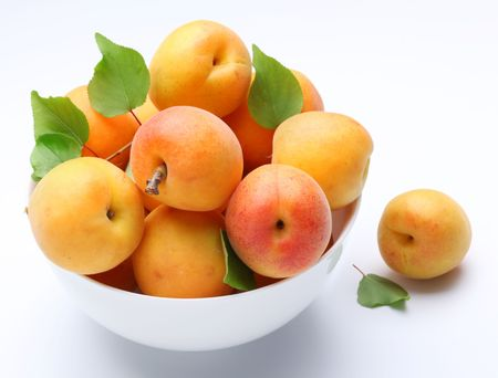 mellow: Crockery with mellow apricots. Isolated on a white background.