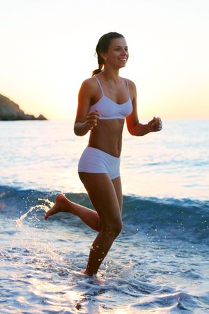 sensational: Sexy brunette is running on the beach