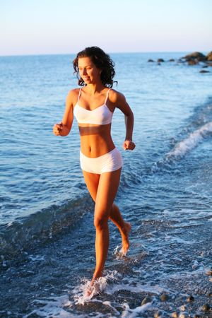 Sexy brunette is running on the beach Stock Photo - 7732045