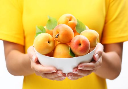 mellow: Woman hands keeping crockery with mellow apricots.