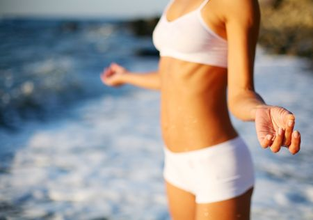 body of a beautiful girl in a meditation on the beach Stock Photo - 7732061