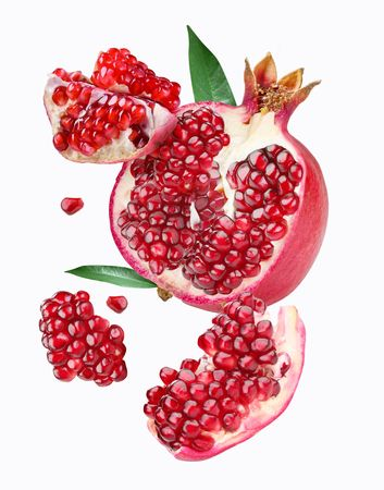 Falling pomegranate slices. Isolated on a white background. photo