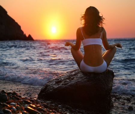 alternative wellness: Woman meditating on the beach at sunset.