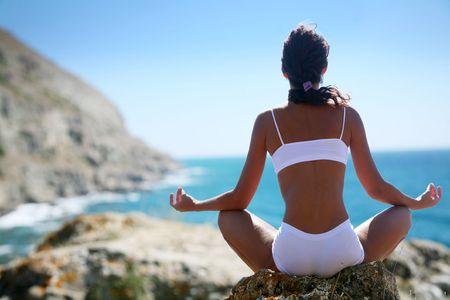 mujer meditando: Mujer meditando en una costa rocosa