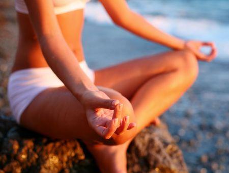mind body soul: corpo di una bella ragazza in una meditazione sulla spiaggia Archivio Fotografico