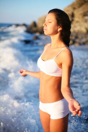 girl meditates standing in the surf. photo