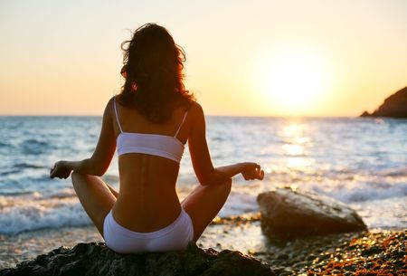 Woman meditating on the beach at sunset. photo