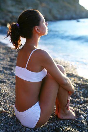 mujer meditando: Mujer meditando en la playa al atardecer.  Foto de archivo