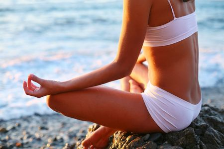 body of a beautiful girl in a meditation on the beach Stock Photo - 7836296