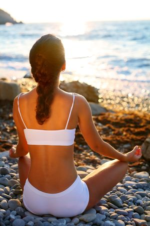 center position: Woman meditating on the beach at sunset.