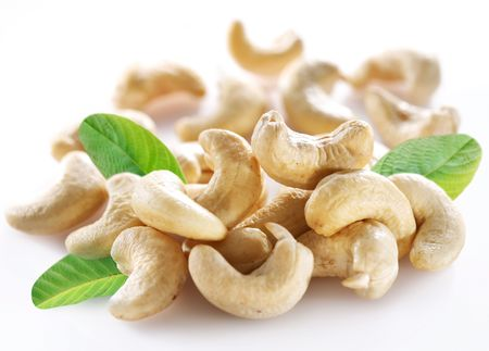 Ripe cashew nuts with leaves on a white background. photo