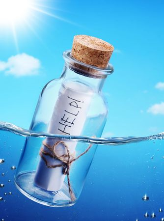 Bottle with help message floating in the see waves. photo
