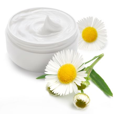 Opened plastic container with cream and camomile on a white background. Stock Photo