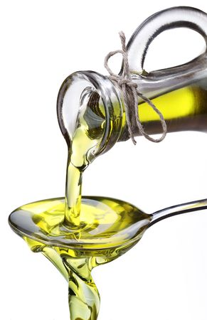 carafe: Olive oil flowing from carafe into the spoon isolated on a white.