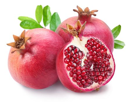 crimson colour: Juicy opened pomegranate with leaves. Isolated on a white background.