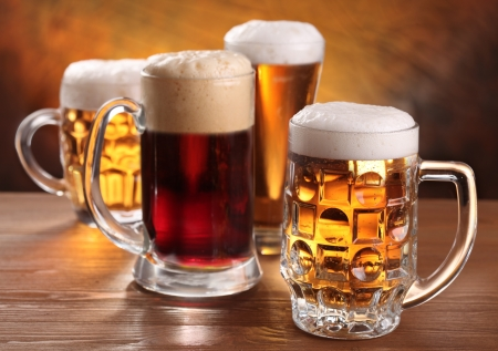 pitcher: Cool beer mugs over wooden table.