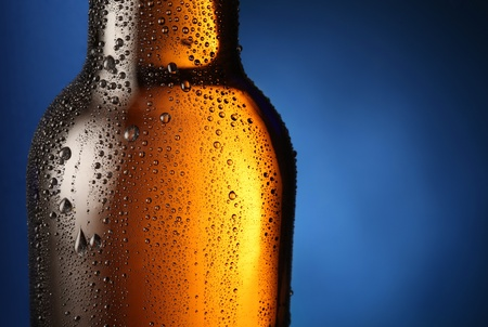 dewed: Bottle of beer with drops on a blue background. Close up part of the bottle.