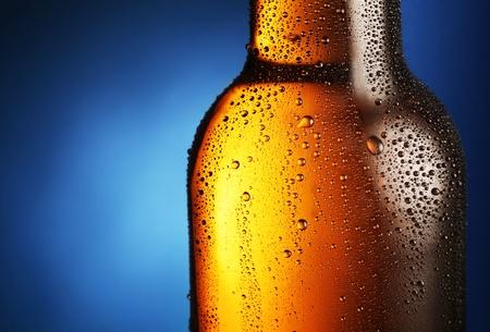 bier glazen: Flesje bier met druppels op een blauwe achtergrond. Close up deel van de fles. Stockfoto