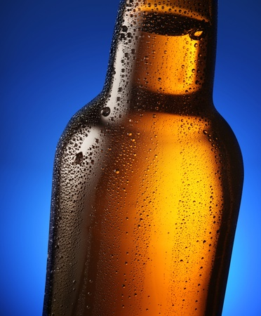 Bottle of beer with drops on a blue background. Close up part of the bottle. Stock Photo - 8296252