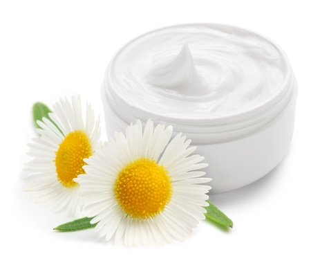 camomiles: Opened plastic container with cream and camomile on a white background. Stock Photo