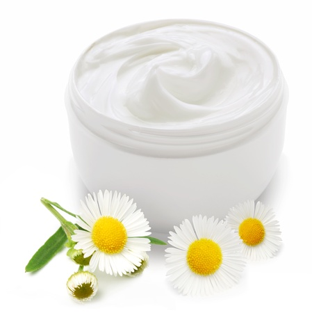 cream: Opened plastic container with cream and camomile on a white background. Stock Photo