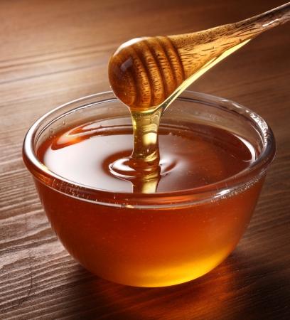 frasco: Miel a raudales de drizzler en el recipiente. Taz�n est� en una tabla de madera.